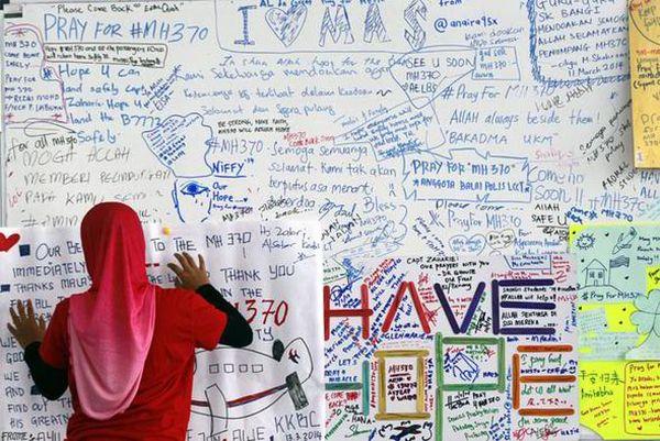 Seorang wanita menulis simpatinya di sebuah banner atas hilangnya Malaysia Airlines. (Foto: EPA)