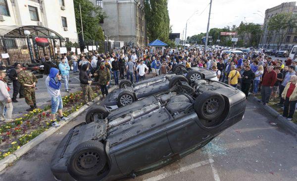 Dua mobil diplomat di terbalikan oleh pengunjuk rasa saat demonstrasi di depan kantor Kedutaan Rusia di Kiev (Foto: Reuters)