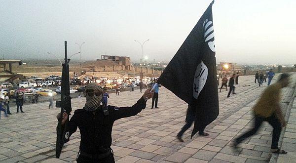 Salah seorang pengikut memegang bendera ISIS. (Foto: Reuters)