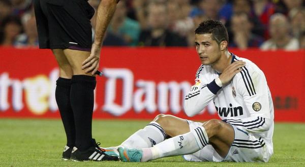Cristiano Ronaldo memegangi bahunya yang mengalami cedera ketika Madrid lawan Barca (Foto: Reuters)