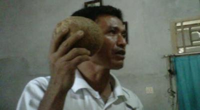 Rustam memegang buah kelapa yang bisa bersuara (Foto: Okezone/Tri Purna Jaya)