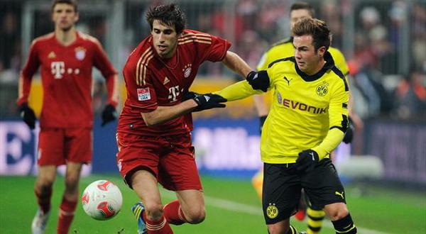 Javi Martinez berduel dengan Mario Gotze yang mulai musim depan akan berkostum Bayern (Foto: Reuters)