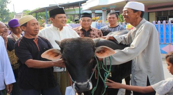 Bambang (kanan) memegang lembu korbannya (Foto: Arie Yoenianto/Koran